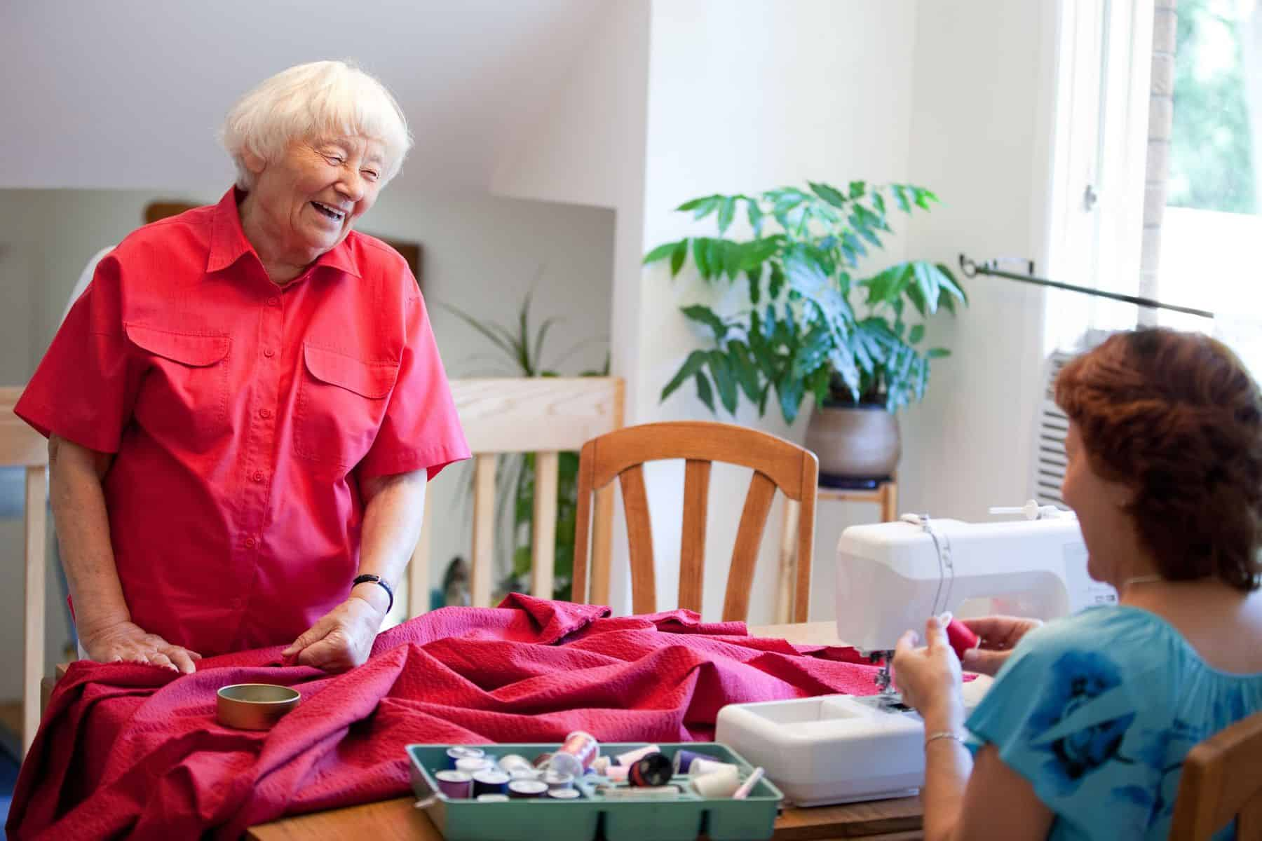 Volunteer helping senior with sewing project