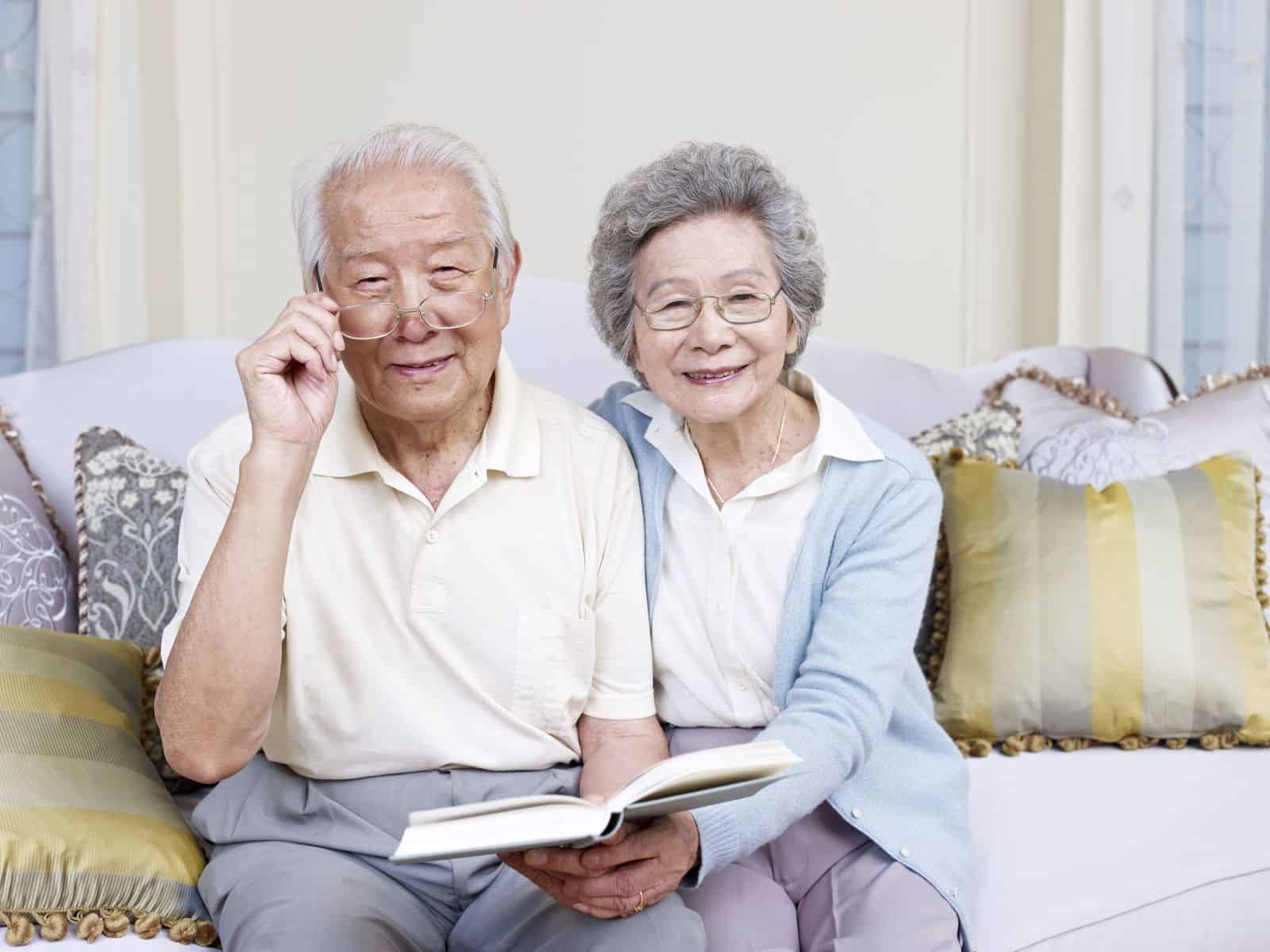 two elderly people reading a book and looking at camera