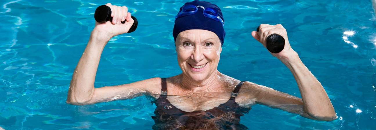 older lady holding dumbells in water aerobics class